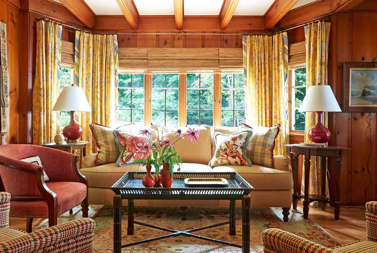 Warm yellows, red, and teal dominate in the cozy TV room of the main residence, which was designed by Jennifer Schuppie of Peabody's Interiors, and Jose Carlino of Jose Carlino Design. The pine walls are original to the house, and the space is anchored by a sofa and houndstooth armchairs from Lee Industries.