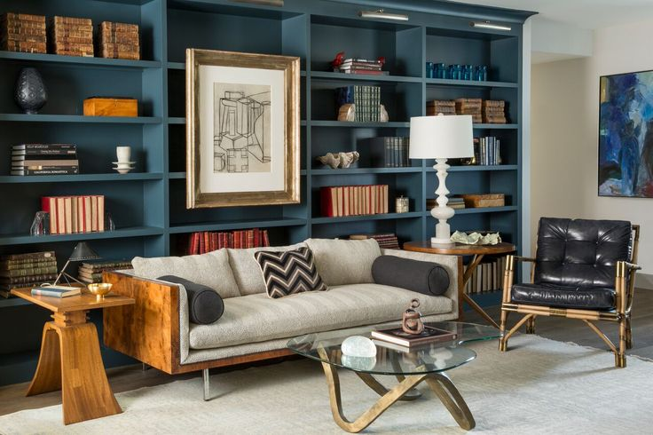 A library featuring blue built-in bookcases and a cozy sofa. Do you like the mix of wood grains in the furniture? Designed by http://wickdesign.com/
