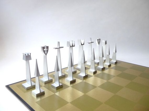 Highly sought after extruded aluminum chess set designed by Austin Cox for ALCOA. This set is an earlier model given as gifts to ALCOA employees and includes a worn black leather carrying case for the pieces. Reversible matte/gloss laminate chess board is signed: What Next From ALCOA?.