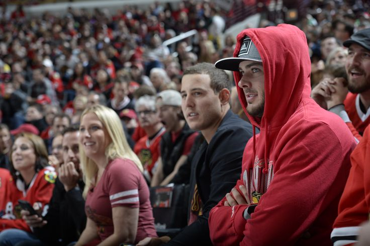 Anthony Rizzo #44  of the Chicago Cubs sits next to teammate Kris Bryant #17 as they watch the Blackhawks take on the Minnesota Wild.