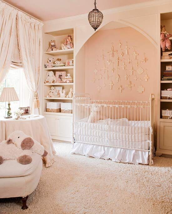 Comfort is key in this beautiful baby's room. A white crib is nestled in a cozy alcove with fluffy white bed linens. A collection of crosses above the crib spark creativity. Shelves on either side of the alcove boast space for all of baby's belongings, and the heavy cream curtains over Roman shades promise to keep out unwanted light at naptime.