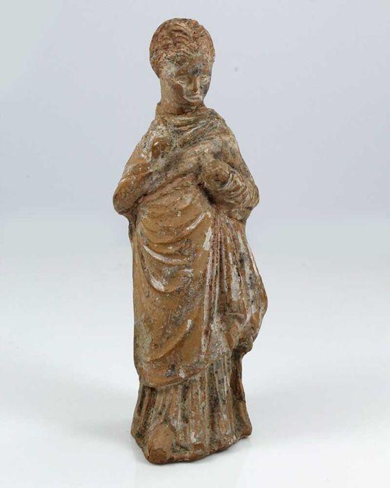 Een Hellenistische beeldje van een jong meisje - H. 13 cm (5 inch)  Dit kleine zoete beeldje wordt permanent haar armen worden gesteld en is enigszins uitbreiden over haar lichaam maken een contrast tussen de horizontale plooien van gordijnen over haar borst en de verticale plooien van weefsel dat zich uitstrekt van haar taille tot haar voeten. Haar himation volledig omhult haar lichaam en haar handen omvat. Haar haar is verdeeld in secties van gedraaide strengen en verzameld in een broodje…