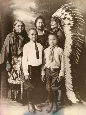 Here is a 1900 family from the Comanche Nation. The elder man is Ta-Ten-e-quer and his wife, Ta-Tat-ty. Their niece is Wife-per or Frances Wright. Her father was a Buffalo Soldier who deserted and married into the Comanches. Henry (left) and Lorenzano (right) are the sons of Frances. Within the fabric of American identity is woven a story that has long been invisible—the lives and experiences of people who share African  and First Nation descent, their double heritage is truly indivisible.