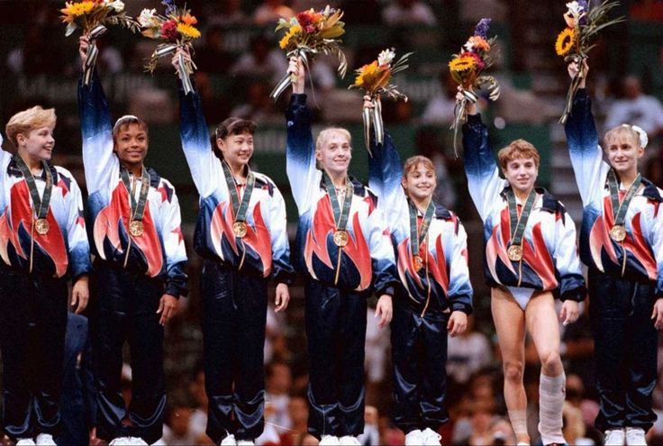 The U.S. women's gymnastics team members (including Shannon Miller, right) accept their gold medal in the team competition in 1996 to the cheers of the home country crowd in the Georgia Dome. AJC FILE PHOTO