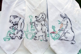 Tea towels embroidered with animals chowing down from the White Elephant Sale.