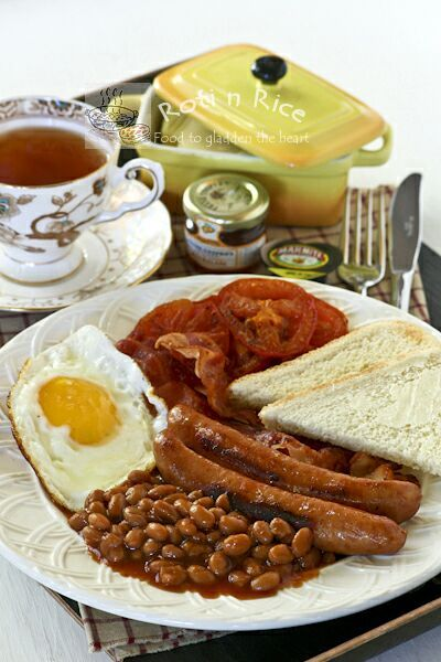 A fully cooked English Breakfast of bacon, eggs, sausages, pan fried tomatoes, and baked beans together with marmalade or Marmite toast and a cup of tea. | Roti n Rice