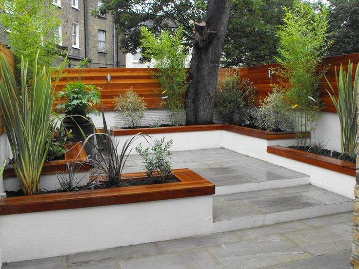 Rendered concrete block walls painted chalk, dove grey riven sandstone paving, raised beds with hardwood caps, floating balau hardwood bench, stainless steel up and down wall lights, bamboo, phormium and mixed contemporary planting complete the scheme - London