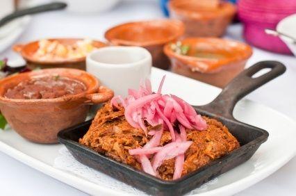 La cochinita pibil es un plato típico de la región de Yucatán en México. Antiguamente los mayas lo cocinaban en un horno subterráneo, ahora se puede preparar en un horno convencional dejando marinar toda la noche. Se sirve con salsa de cebolla.