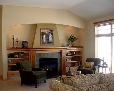 This fireplace is uniquely situated in an alcove which gently emphasizes the fireplace and shelves.