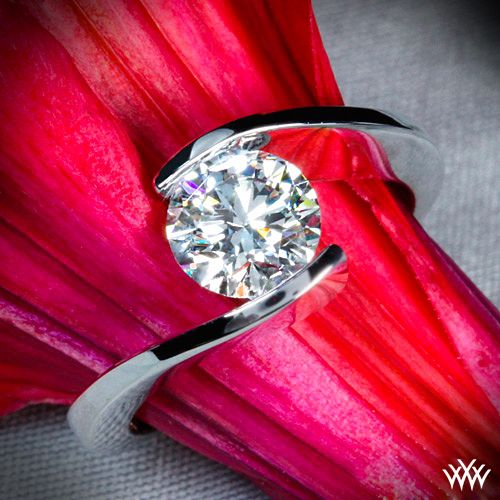 """Unique and alluring, the """"Lilly"""" Solitaire Engagement Ring puts a special spin on classic solitaire designs. The tension style setting ensures total security for your diamond without hindering brilliance and shine."""