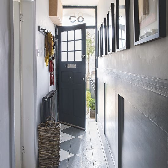Hallway with blue open front door and painted floorboards