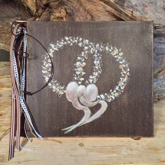 Χειροποίητο δερματόδετο βιβλίο ευχών με ξύλινα εξώφυλλα σε καφέ antique χρώμα με δύο στέφανα στο εμπρός μέρος και διάφορες κορδέλες σε καφέ και ιβουάρ αποχρώσεις στο πλάι.Μπορεί να γραφτεί η ημερομηνία του γάμου καθώς και τα ονόματα του ζευγαριού.http://nedashop.gr/gamos/vivlio-eyxon-gamoy/xeiropoihto-biblio-eyxon-gamoy-stefana