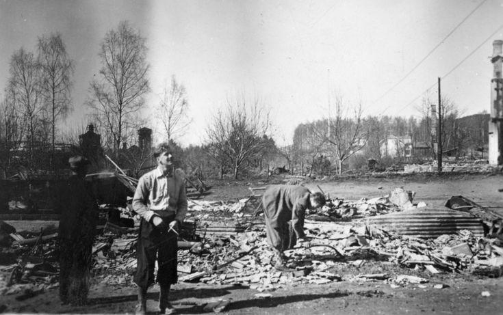 Branntomtene ved Kilde skole, juni 1940. Fire brannruiner, den borterste hos kjøpmann Haugen. Midt i bildet ser vi en person med vedsag., I forgrunnen Ahlsens hus og anleggene og disponentboligen til Cellulosen.  Husene ble skutt i brann av tyske soldater i aprildagene 1940. 2. verdenskrig.