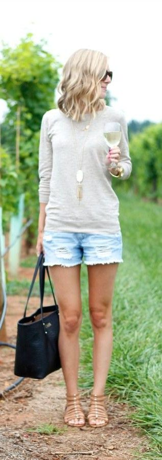Easy and comfortable outfit to wear on trip - denim shorts, beige sweater, flat sandals and black handbag, sunglasses. Blond natural wavy hairstyle.