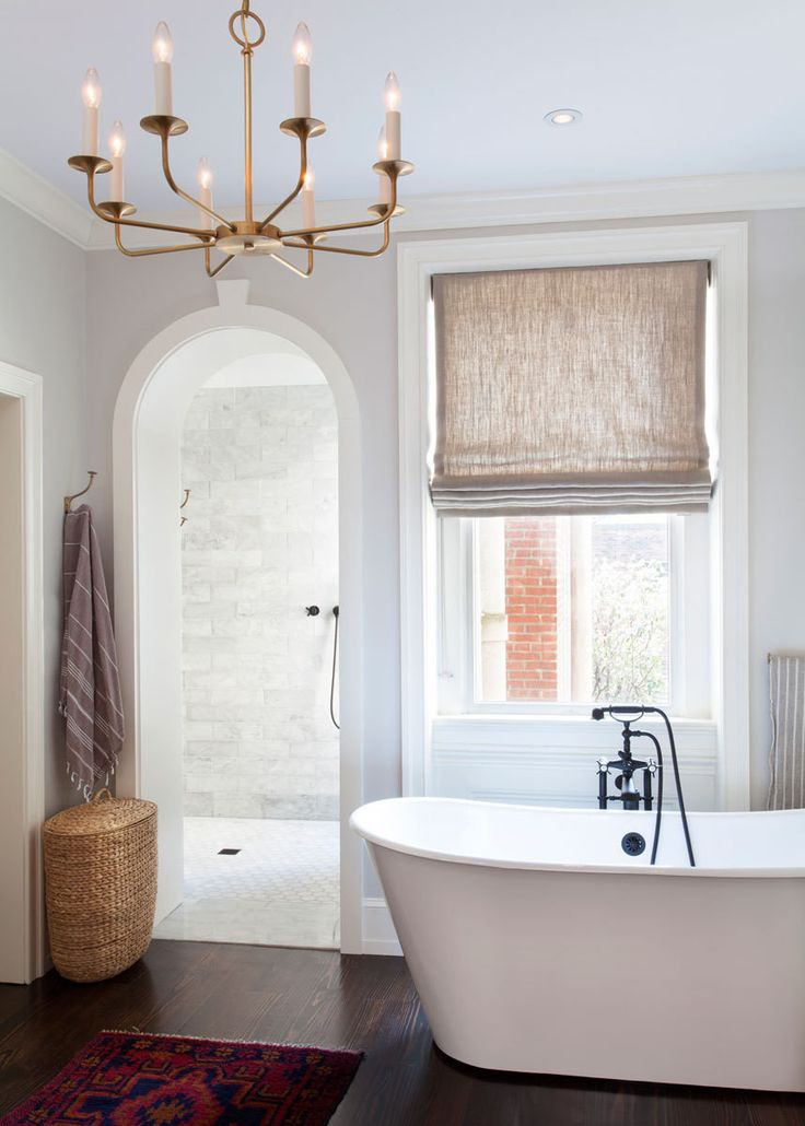 Gray bathroom with hardwood floors, white tub, linen roman shades, marble subway tile, brass chandelier - A Colonial Home with a Contemporary Twist