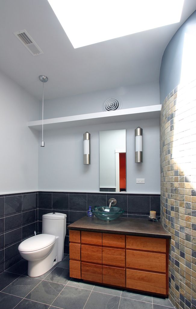 Who says walls have to be straight? Check out this funky curve (which contains the shower), plus how seamlessly it fits with the simple and stylish sink area. High shelves allow for extra storage that eliminates clutter. #bathroom #style #contemporary #sink #renovation #remodeling #construction