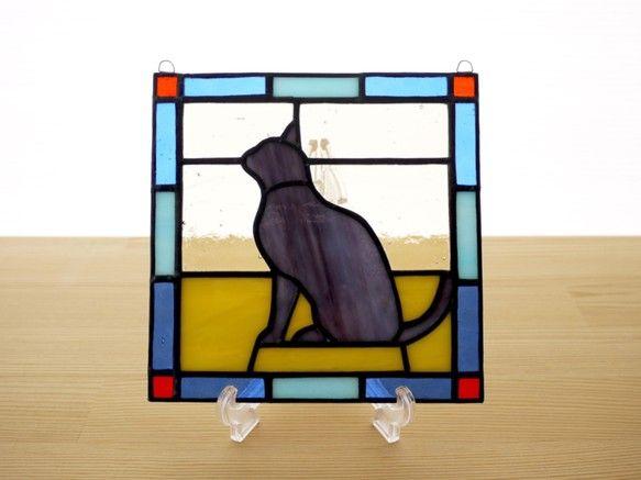 シックな猫モチーフのステンドグラスパネルです。猫の毛の色は落ち着いた雰囲気の、グレーがかった紫のグラデーションです。 パネル上部には吊り下げ用の金具が付いていますので、お手持ちのチェーンや紐で吊り下げて飾ることができます。陽のあたる窓際に吊り下げると、ガラスの色が鮮やかに(濃く)浮き上がり、とてもきれいです。作品は自立しませんが、壁に立てかけたりお手持ちの皿立てに立てかけて飾ることも可能です。その場合は倒れて割れないよう布などを敷くことをお勧めします。 同サイズの作品をいくつか並べて飾っても素敵です。DIYが得意な方は、ドアや壁にはめこんたり額に入れて飾ってみてはいかがでしょうか。大きさ:たて約15cm×よこ約15cm×厚さ約3mm 重さ:約200g 素材:ガラス、鉛●ご購入の前に必ずご確認ください。作品はすべてハンドメイドの一点ものです。 ガラス作品のため、光のあたり具合によって色の見え方や透明感が違ってきます。…
