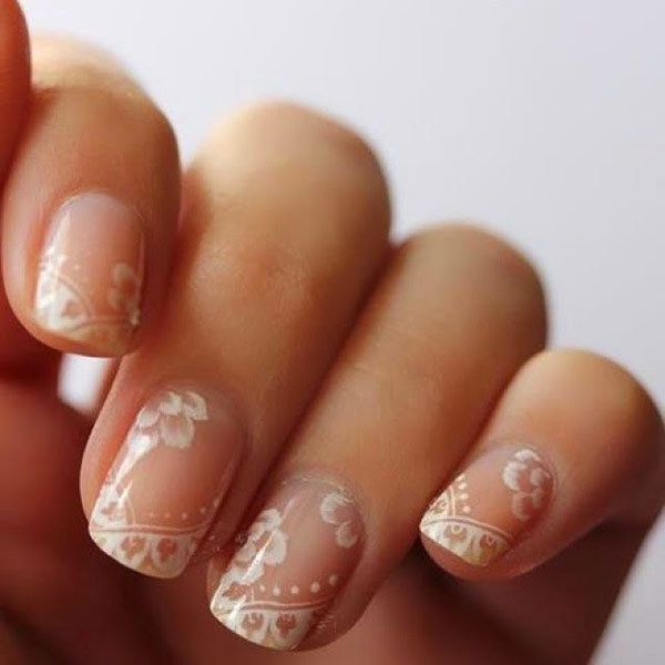 Nude and white lace nails for a detailed bridal manicure.