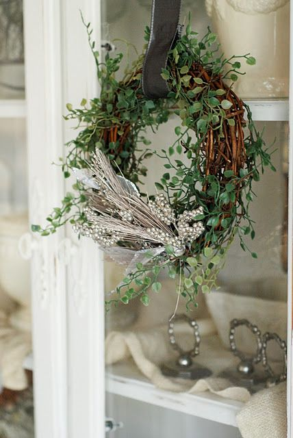 A Sweet little Grapevine Wreath::Decorated with greenery and frosted branches and hung with a wide piece of ribbon.