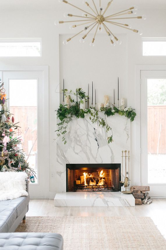 white marble fireplace with fresh green