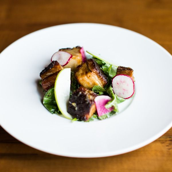 Garam Masala Pork Belly with Apple Frisee Salad & Tamarind Gastrique. Recipe from Maneet Chauhan. Photo by Andrea Behrends.
