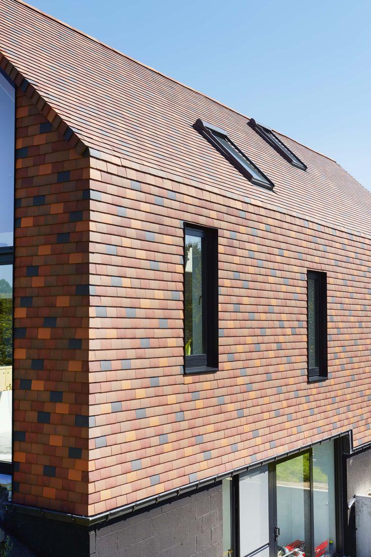 Gezinswoning uit één stuk in Lubbeek (Zampone Architectuur, Sint-Jans-Molenbeek). De woning is opgevat als één massieve sokkel die samen met het bovengelegen volume volledig met tegelpannen is bekleed. Voor de bekleding van zowel dak als gevels viel de keuze op Koramic tegelpannen in een kleurenmix van aardetinten. Aangepaste elementen zorgen voor een naadloze overgang tussen gevel en dak. Het gebruik van diverse rode tinten geeft de woning een sprankelend uitzicht.