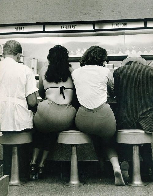 Two women share a stool at the diner, 1950s. I adore that the one without a shirt on has heels on & the one with a shirt on is barefoot <3