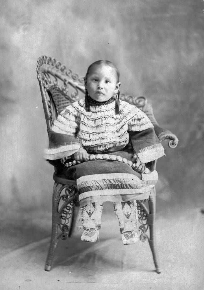 Studio portrait of a Native American Dakota Sioux girl seated in a wicker chair. - 1890/1910