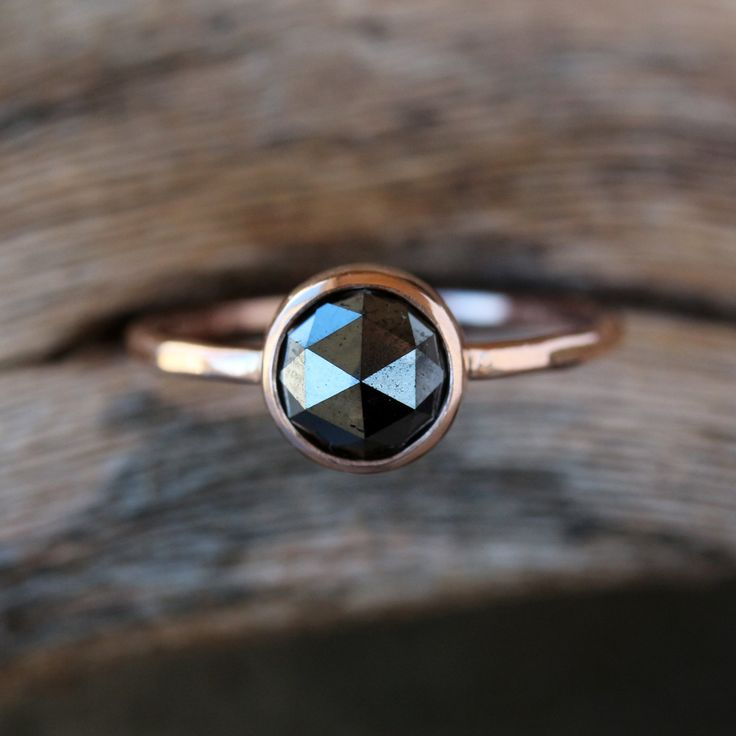 A beautiful, rose cut black diamond sparkles in a simple 14k rose gold setting atop a lightly hammered 14k rose gold band. The hammering technique I use on the band creates a faceted effect for a gorgeous play of light. Rose gold and black diamonds are a match made in heaven! A rose cut diamond has a flat base and a crown made up of triangular facets that are symmetrically arranged and rise to form a rounded point at the top of the stone. The look is old-world and antique-inspired. Please…
