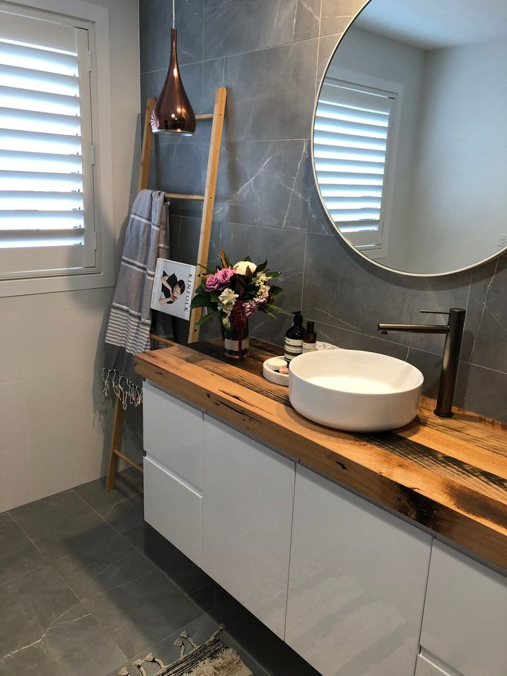 Gun metal finish tap wear, recycled timber vanity top and cool grey and white floor and wall bathroom tiles.