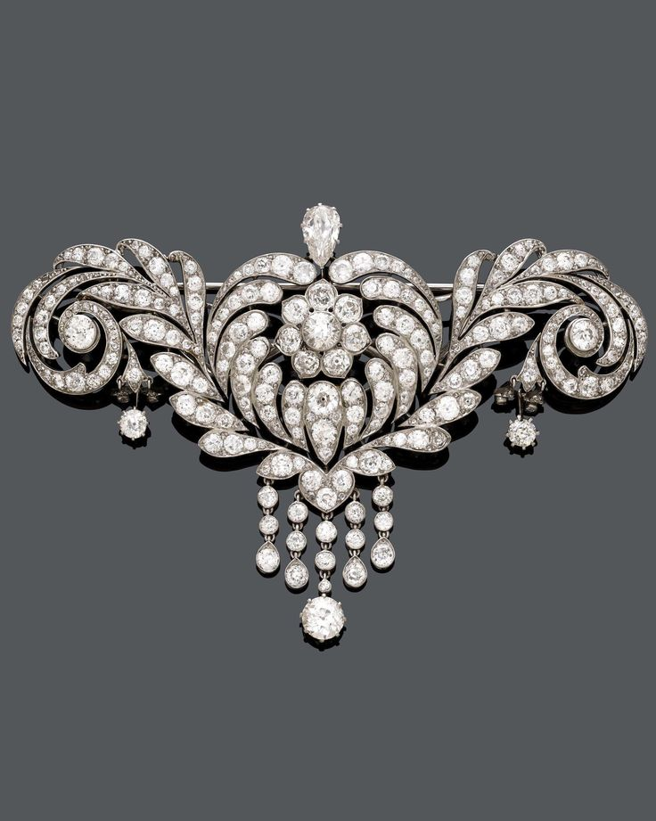 A BELLE EPOQUE PLATINUM AND DIAMOND CORSAGE-BROOCH, CIRCA 1910. Designed as an openwork flower with rolled-up leaves set with 1 pear-shaped diamond and numerous circular-cut diamonds, suspending 5 diamond-set pendants. 9.7 x 7.6cm. #BelleÉpoque #corsage #brooch