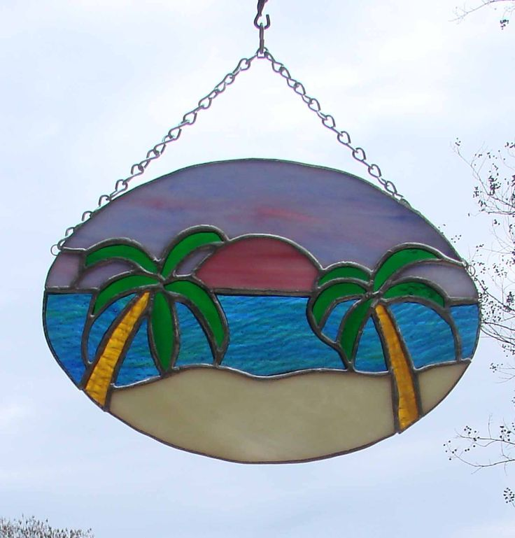 """Sunset on a Tropical Beach Handmade Sunrise Stained Glass Panel Sun Catcher. This tropical beach sunset scene is perfect for the beach lover on your gift list. The glass I used for the sky is a gorgeous pastel swirl of pinks and purples and the water is a textured blue green mix ripple glass. These ripples catch the light and make the water shine as if it is moving. The glass in the palm tree trunks is also textured and looks like real tree trunks. Dimensions:8 3/4"""" by 6 1/4"""" Oval This…"""