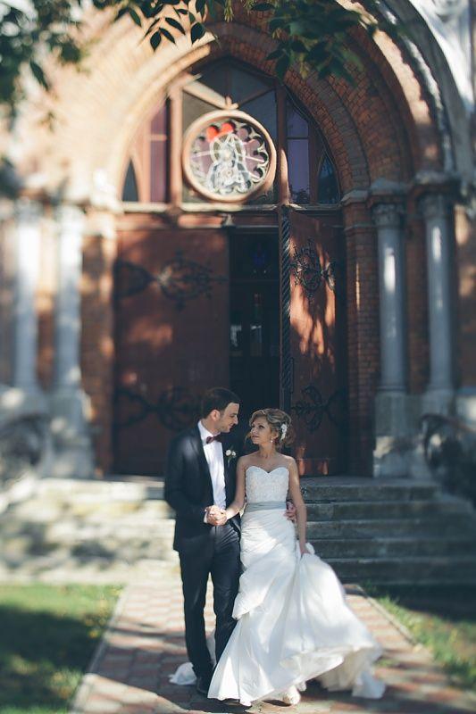 Жених обнимает невесту за талию и вместе они идут на камеру, смотря друг на друга.