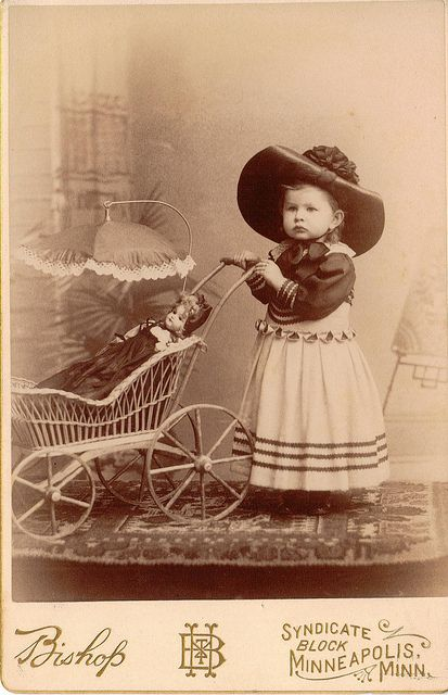 Fancy-dressed little girl with her doll in a wicker carriage with a parasol top.