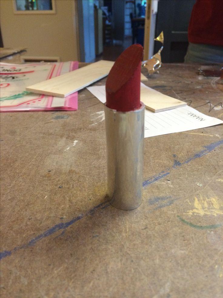 Dit is het resultaat van mijn lipstick. Ik heb het hout rood geverfd zodat het wat meer op een lipstick leek. De huls en het houtje waren alleen niet even breed geworden, waardoor het houtje steeds uit de huls gekleed. Ik heb daarom het houtje wat verdikt met papier en op het papier lijm gesmeerd, zodat het wat beter bleef zitten.