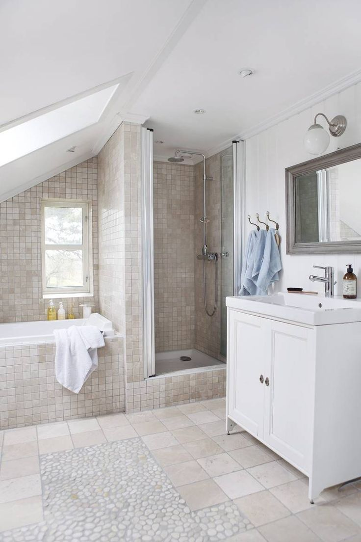 LYST OG LEKKERT: Dette badet er innredet med forskjellige fliser i samme fargetoner. Den steinlignende overflaten og sandfargen gir rommet en rustikk følelse med assosiasjoner til naturen. Servantskapet og krokene på veggen tilfører en landlig touch.