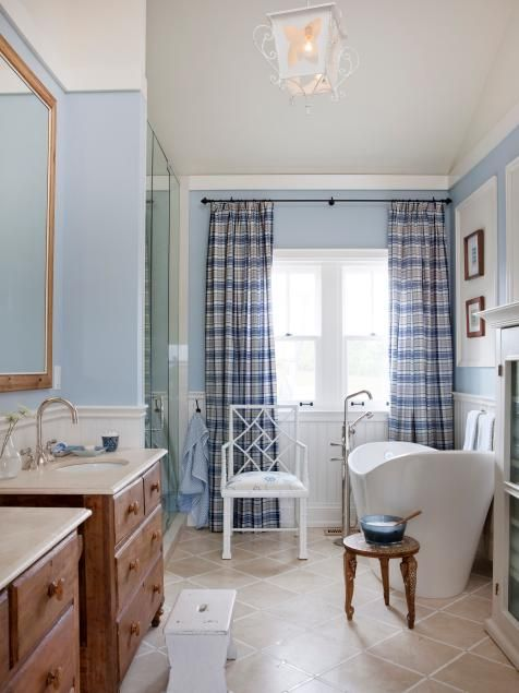 Designer Sarah Richardson of Sarah's House creates a family-friendly bathroom with a classic blue-and-white palette. For an updated country style, she repurposes a pair of antique chest of drawers as vanities and hangs cheery checked curtains. A deep soaker tub with a modern silhouette brings a freshness to the space.