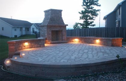 raised patio area with retaining wall and fireplace