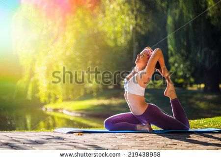 Young woman doing yoga in morning park near lake  - stock photo