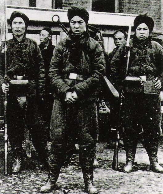 Boxer soldiers, dressed in black and carrying traditional weapons