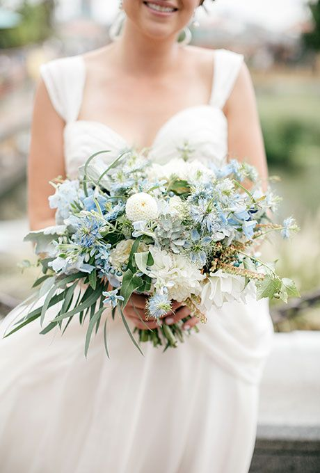 A blue-and-white bouquet comprised of tweedia, peonies, greenery, and berries, created by Leaves of Grass Floral Design.