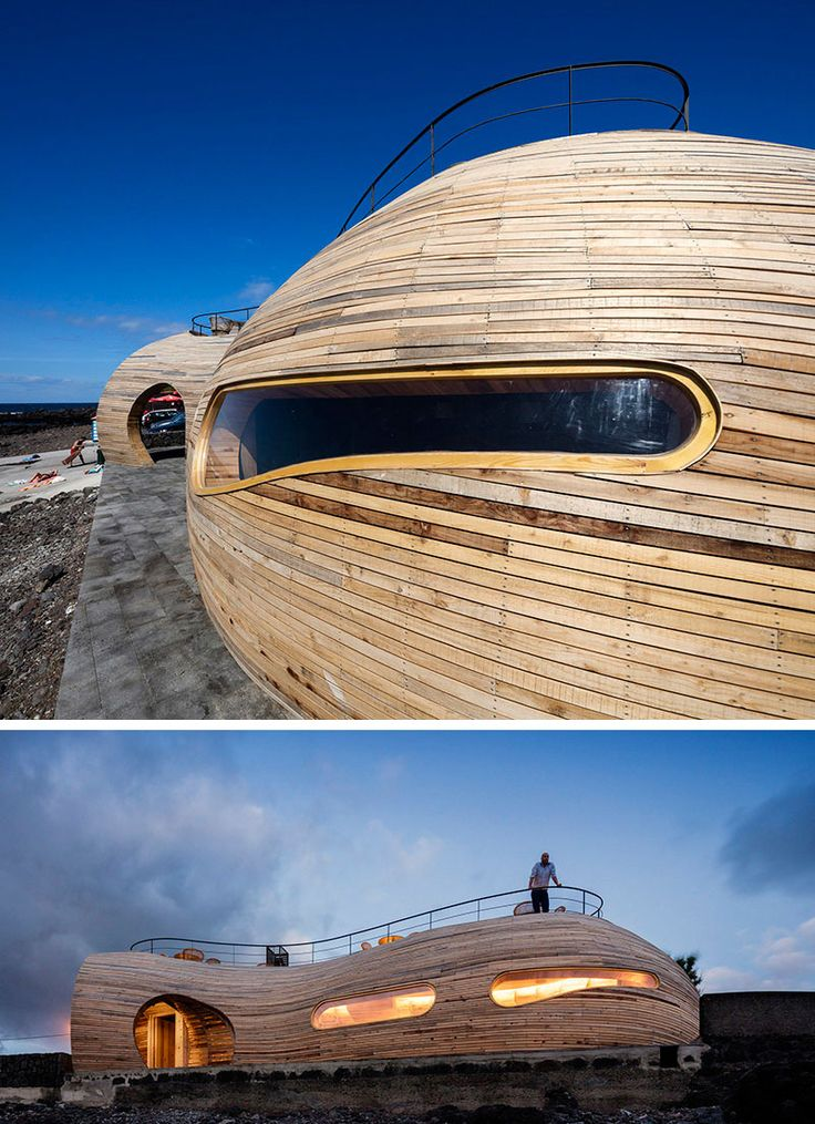 The sculptural exterior of this modern bar has long windows that organically flow with the wood building, and reveal a glowing interior at night.