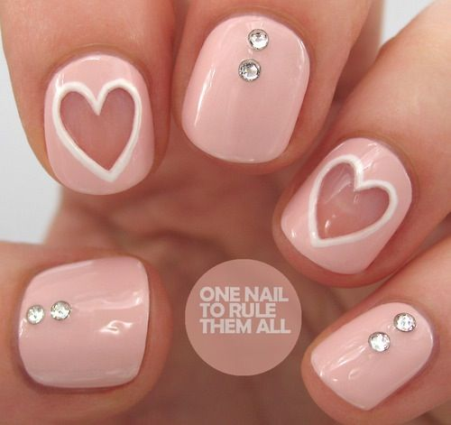 Light pink nails with crystals and peek a boo hearts.