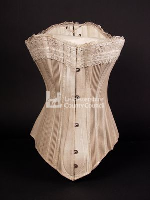 This corset was produced in 1885 and is made from a fawn coloured twill, which has been interlined with hessian. It is supported by heavy string cording and has a spoon busk at the front.