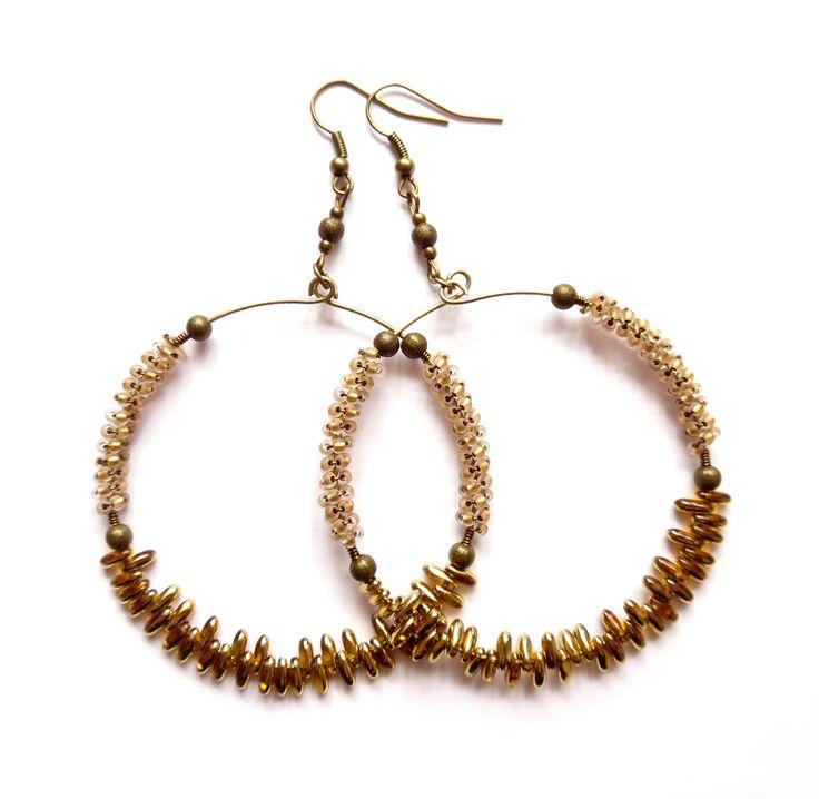 Örhängen med stora ringar i brons och bruna pärlor av glas.  Längd: 9cm