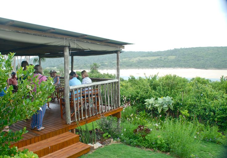 Sibuya Game Reserve guests having tea on the deck while waiting to go by boat along the Kariega River to Forest Camp. At Kenton on Sea, Eastern Cape, South Africa