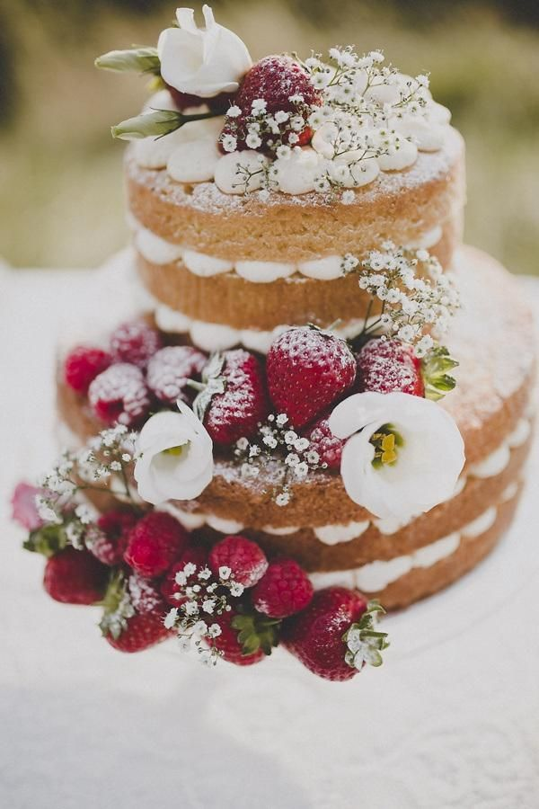 Bohemian Countryside Wedding Ideas - Weddbook...I love the strawberries mixed with fresh flowers that are decorating this cake. If it were frosted underneath those beautiful decorations, this would be a gorgeous cake!