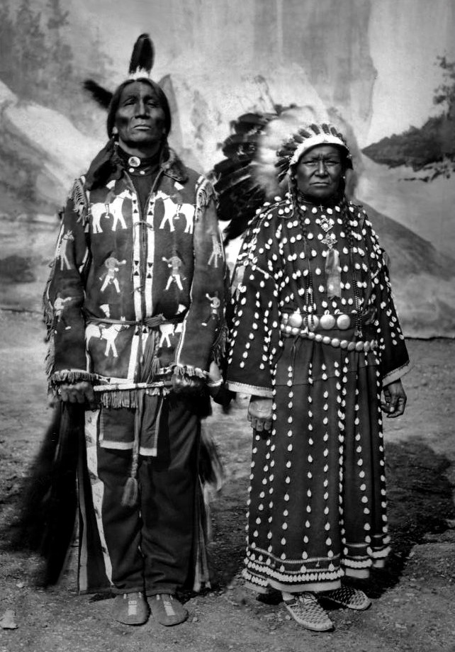 "Sioux man Spotted Weasel and his wife, members of ""The Red Man spectacle and Red Indian camp"" stand in front of a painted backdrop of Yellowstone Falls in the dirt arena in Empress Hall, at the Golden West and American Industries Exhibition in Earl's Court, London, England. Photo: 1909."