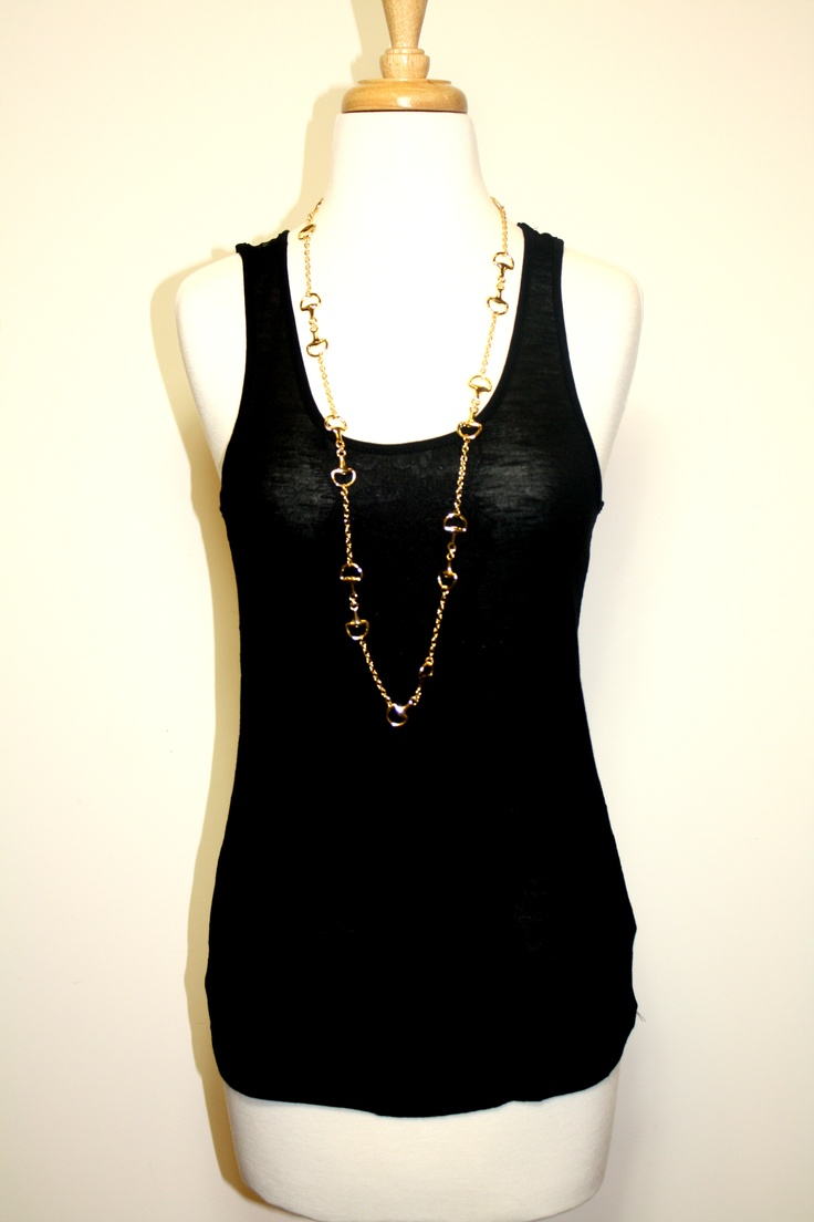 Our lace-detailed black camisole is worn with a long gold saddle necklace- great for layering!