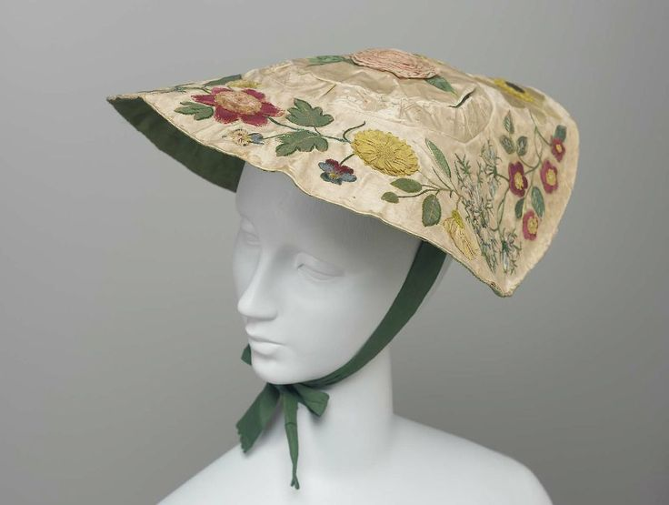 Hat: ca. 18th century, French, satin round disk-like base, variety of flowers on brim and crown, lined with twill, two silk ribbons.